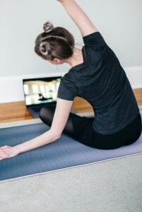 на фото девочка делает упражнения для спины перед ноутбуком